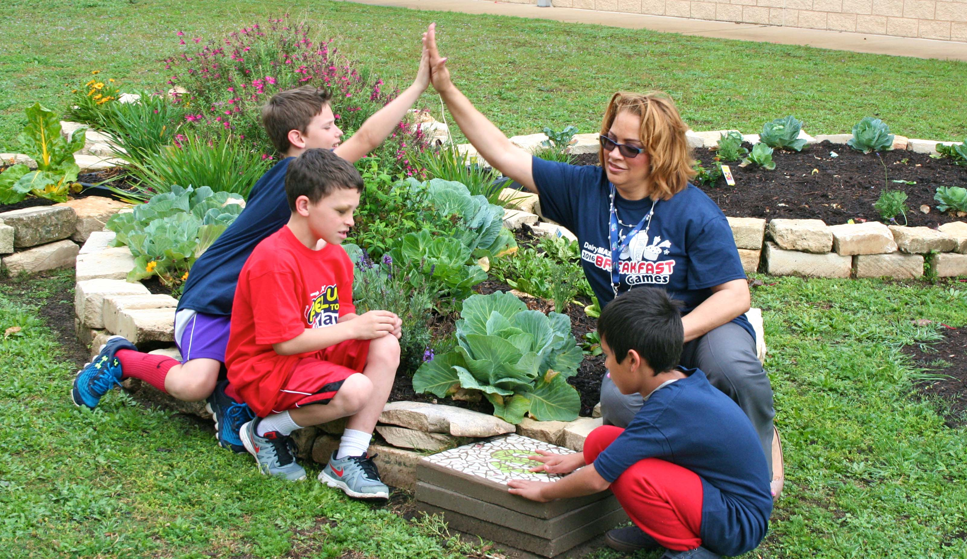 Angela Olige in garden at Pleasant Hill Elementary with students.
