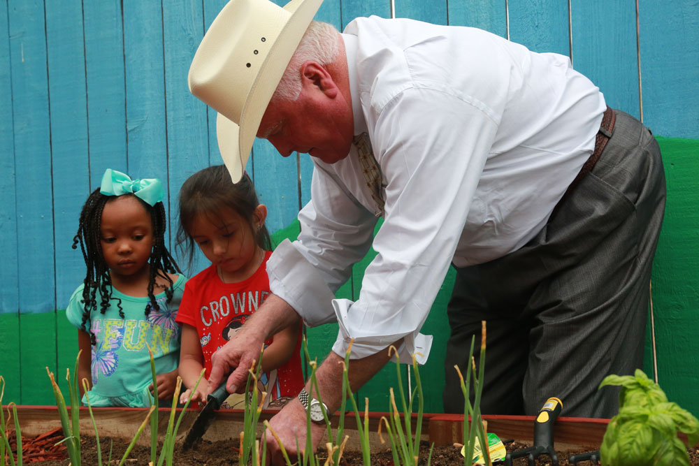 Commissioner Miller assists Kids R Fun students with planting.